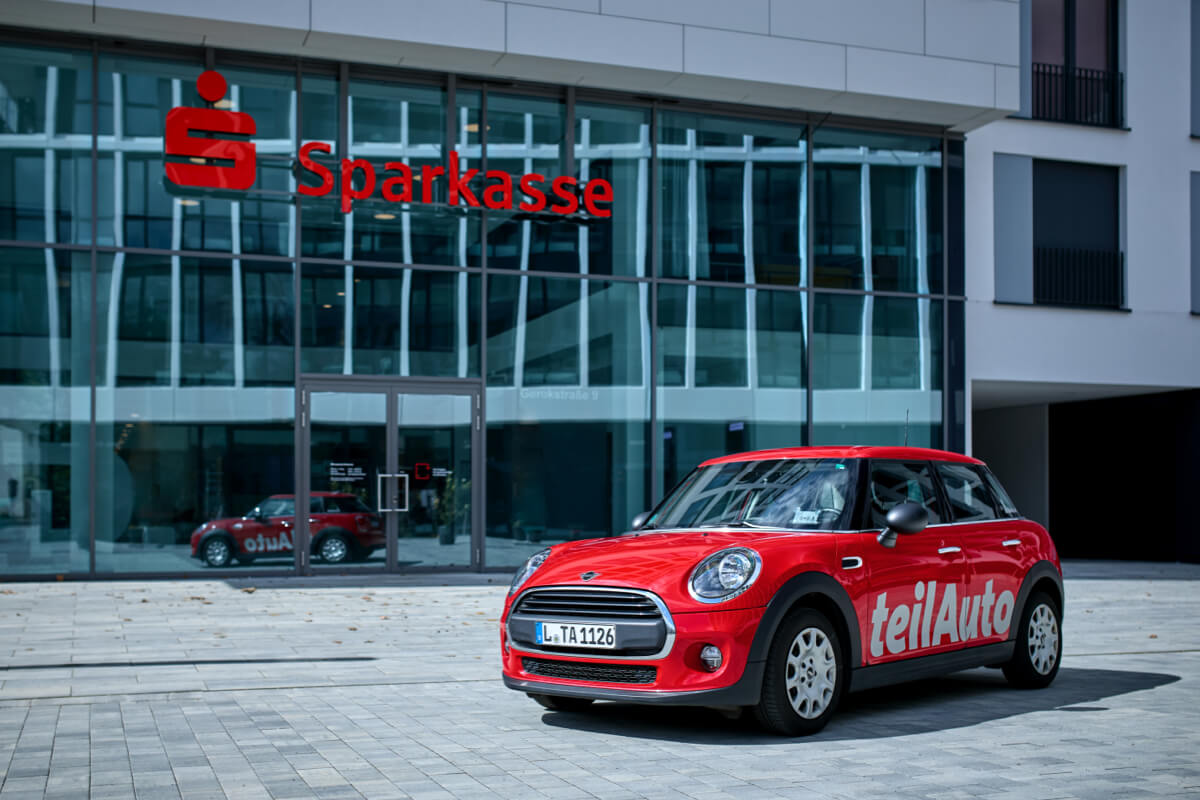 Roter MINI vor Sparkasse - teilAuto Carsharing